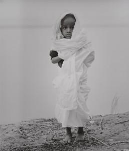 《インド 永遠の光》より、髪を剃られて喪主の装いを纏うチタドゥはまだ5歳。     次々と両親を亡くし、残った最期の家族である。夕暮れのナランプール火葬場にて。2013年2月