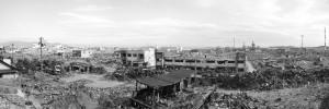 《石巻市定点撮影 2011/2015 No.3 高台から南浜町4丁目方面を望む(南方向)。 津波により甚大な被害を受けた門脇町、南浜町。海岸の防波堤を越えて約7mの津波が一帯に押し寄せた。ほとんどの住宅や建物は水没し、津波に押し流された自動車から火災が発生し、一昼夜燃え続けた。現在では被災した建物の撤去が進み、一部の区域では区画整理のための造成が始められている。(Ishinomaki City Then and now: Four Years after the Tohoku Earthquake, #3 Overlooking Minamihamacho 4 chome from the hilltop. (Viewing south) Kadonowakicho and Minamihamacho were seriously destroyed by Tsunami. The two towns were struck by 7 meter high Tsunami against which the breakwater along the shore was helpless. Most of the houses and buildings in the town sunk under the water, while automobiles pushed away by Tsunami caused a fire. It kept burning though day and night. By now, rubbles have been removed and some parts of the town are under rezoning.)》2011/2015