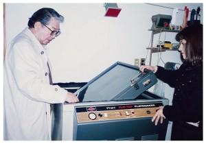 暗室にて。細江館長(左)が動かしているのは、ヴァキュームによってネガと印画紙を密着させ、ガラス版を回転させて露光するプリント用機器。